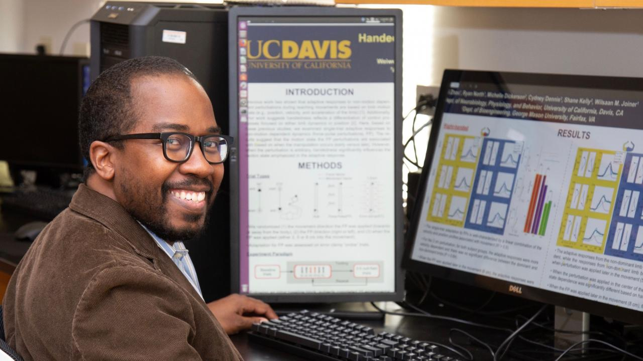 Wilsaan Joiner, PhD, in front of computer showing his research results